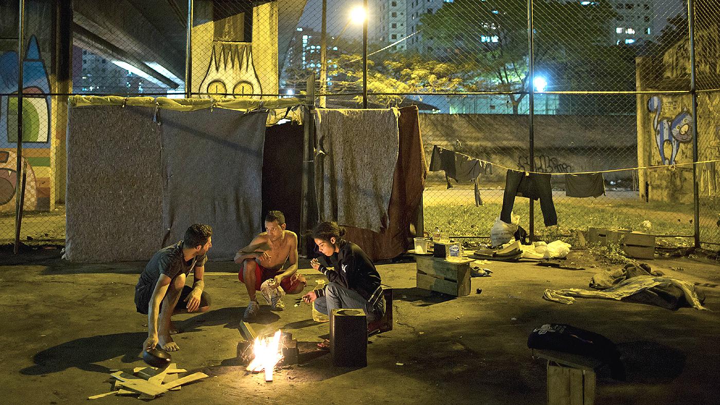 Garotos preparam uma comida em uma fogueira diante do local em que vivem, debaixo de um viaduto em São Paulo (AP Photo/Andre Penner)