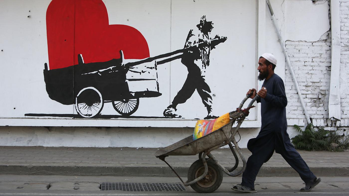 Afegão passa com carrinho de mão em frente a grafite que homenageia seu trabalho (AP Photo/Rahmat Gul)