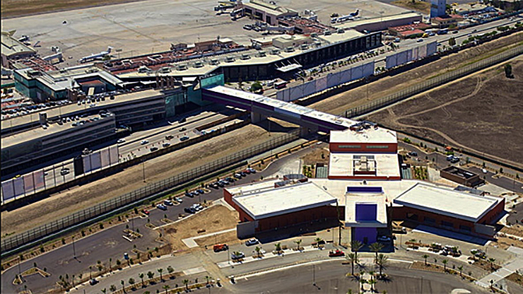 Vista aérea do Cross Border XPress, com a ponte passando sobre o muro da fronteira e o terminal do aeroporto em Tijuana à esquerda